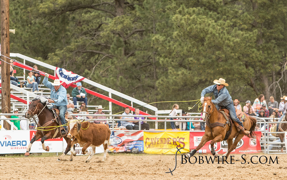 Header Robert Reed and heeler TW Wilson make their team roping run during the third performance of the Elizabeth Stampede on Sunday, June 3, 2018.