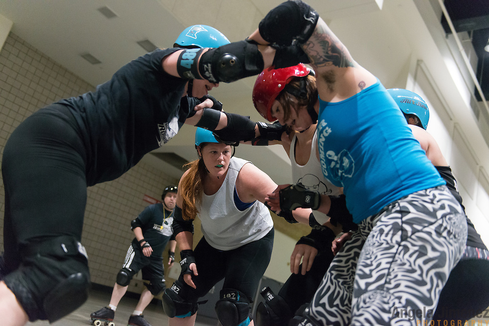 Team captain Diamond Rough (Lisa Eng-Sarne), center in white tank, competes in a scrimmage during Minnesota RollerGirls All-Star team practice at Exhibit Hall B at the Saint Paul RiverCentre in Saint Paul, Minnesota on November 3, 2015. <br /> <br /> The team is preparing to compete in, and host, the 2015 International WFTDA Championships at the Legendary Roy Wilkins Auditorium here in Saint Paul, Minnesota from November 6-8, 2015. <br />  <br /> Photo by Angela Jimenez for Minnesota Public Radio www.angelajimenezphotography.com
