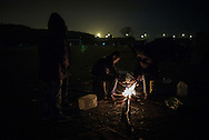 Warming at a wooden fire. Migrants waits for the night to try to hide in the truck
