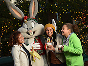 A group friends enjoy hot chocolate served up by Bugs Bunny at Six Flags Over Texas in Arlington, Texas during Holiday in the Park.