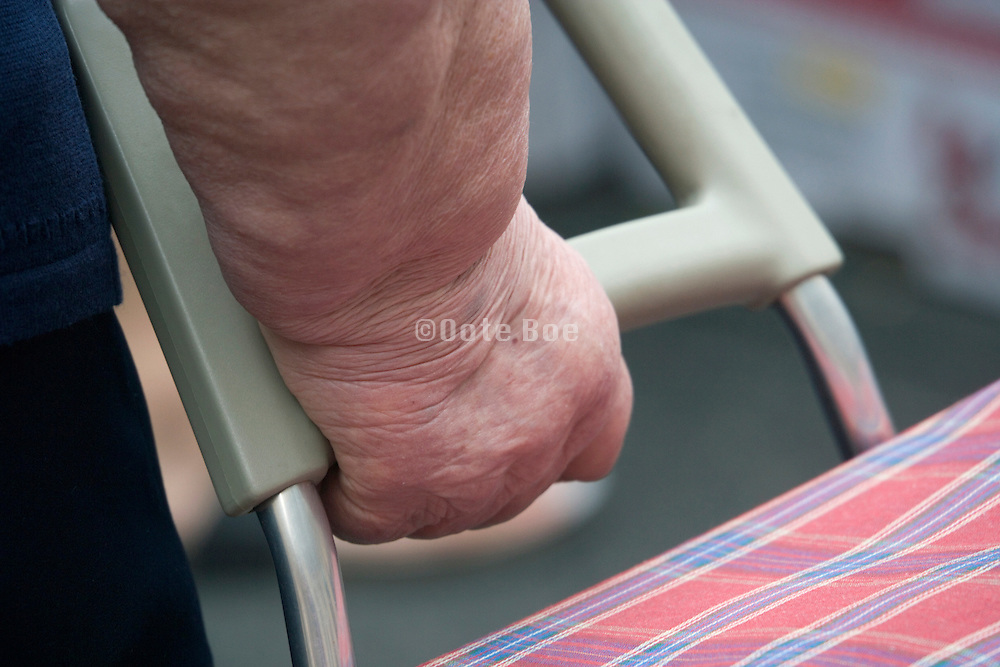 wrist and hand of an obese woman holding here shopping cart on wheels
