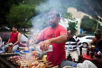 A food vender grills meat skewers at the entrance of Rocinha, in Rio de Janeiro, Brazil, on Friday, Feb. 1, 2013. The community of Rocinha, Latin America's largest favela with an unofficial population of about 250,000 residents. Pacification and police presence have made most of the area safer for both residents and visitors.