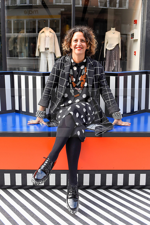 "© Licensed to London News Pictures. 12/09/2019. LONDON, UK.  Artist and designer Camille Walala, poses on one of her sculptural benches at the installation of ""Walala Lounge"", where South Molton Street in Mayfair will be transformed into an urban living room.  10 sculptural benches, accompanied by planters and a series of oversized flags strung, bunting-style, from shopfront to shopfront, will convert the street into an immersive corridor of colour as part of this year's London Design Festival.  Photo credit: Stephen Chung/LNP"