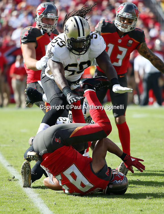 New Orleans Saints outside linebacker Dannell Ellerbe (59) and New Orleans Saints defensive back Kyle Wilson (24) gang tackle Tampa Bay Buccaneers wide receiver Vincent Jackson (83) during the 2015 week 14 regular season NFL football game against the Tampa Bay Buccaneers on Sunday, Dec. 13, 2015 in Tampa, Fla. The Saints won the game 24-17. (©Paul Anthony Spinelli)