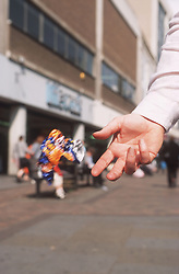 Closeup of adult's hand dropping litter in town centre,