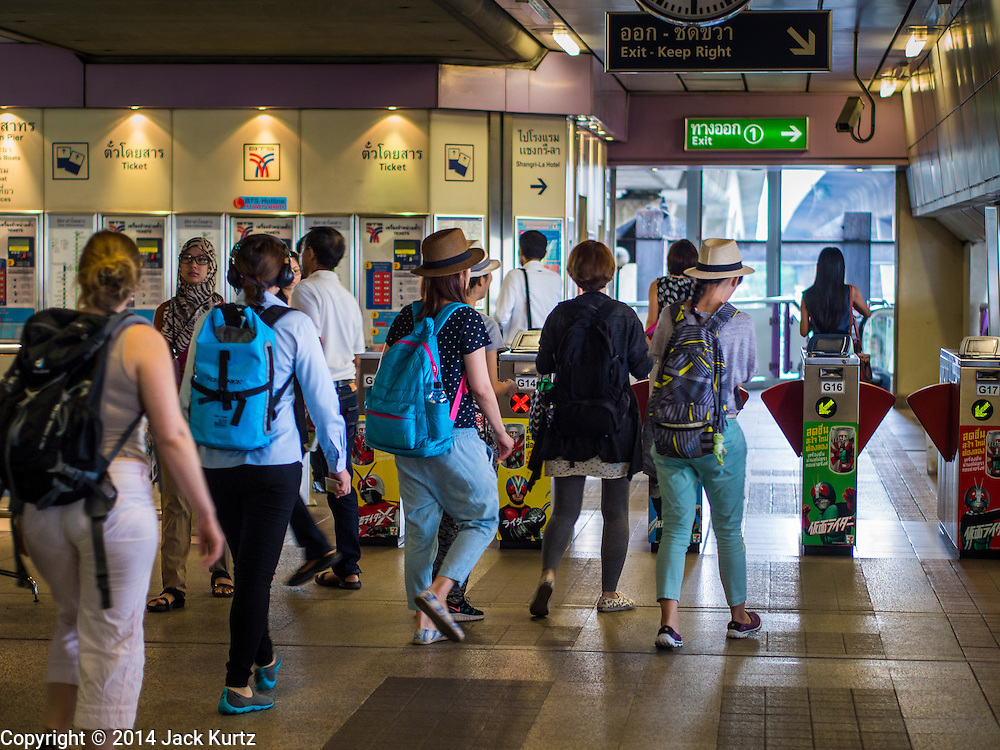 28 OCTOBER 2014 - BANGKOK, THAILAND: Passengers walk through the Saphan Taksin Skytrain station in Bangkok. The Skytrain (called the BTS) system has a combined length of 36 kilometres and includes 34 stations, including Saphan Taksin. While there are two train tracks for most stretches of the Skytrain system, the portion on the Saphan Taksin Bridge spanning the Chao Phraya River has just one track due to limited space, causing a bottleneck when an outbound train and inbound train arrive at the bridge at the same time. The Bangkok Metropolitan Authority (BMA) had sought permission from the Department of Rural Roads to expand the Taksin Bridge in order to make way for an additional track, but the department had said it was not possible. The Saphan Taksin  station was originally supposed to be temporary and is one of the busiest on the system. It's a connecting station for the Chao Phraya River boats used by Thai commuters coming into the city from neighboring provinces and tourists who use the boats to go upriver into the old parts of Bangkok from the central business district. More than 4,000 commuters a day use the station. The BMA plans to build an elevated moving sidewalk to the river from Surasak BTS station about one kilometer away. Surasak is the nearest station to Saphan Taksin. The Skytrain system has a combined length of 36 kilometres and includes 34 stations, including Saphan Taksin.        PHOTO BY JACK KURTZ
