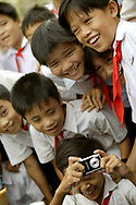 Local Vietnamese boys play with camera while on break from classes outside Saigon