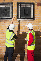 Rear view of two male worker in hardhats pointing towards windows