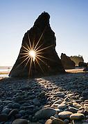 Sun star through a rock opening at Ruby Beach, Olympic National Park, near Kalaloch, Washington
