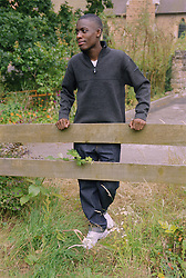 Portrait of teenage youth leaning against wooden fence,