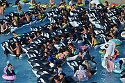 FUSHUN, CHINA - JULY 30: <br /> <br /> People play with inflatable rings and toys at a water park to avoid summer heat on July 30, 2017 in Fushun, Liaoning Province of China. As the temperature reached 32 degrees Celsius in Fushun, people enjoyed themselves in the water park on Sunday. <br /> &copy;Exclusivepix Media