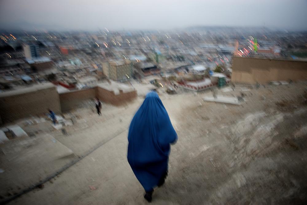 November 17, 2012 - Kabul, Afghanistan: A woman  wearing a burka walks down a hilltop neighbourhood in Kabul. (Paulo Nunes dos Santos)