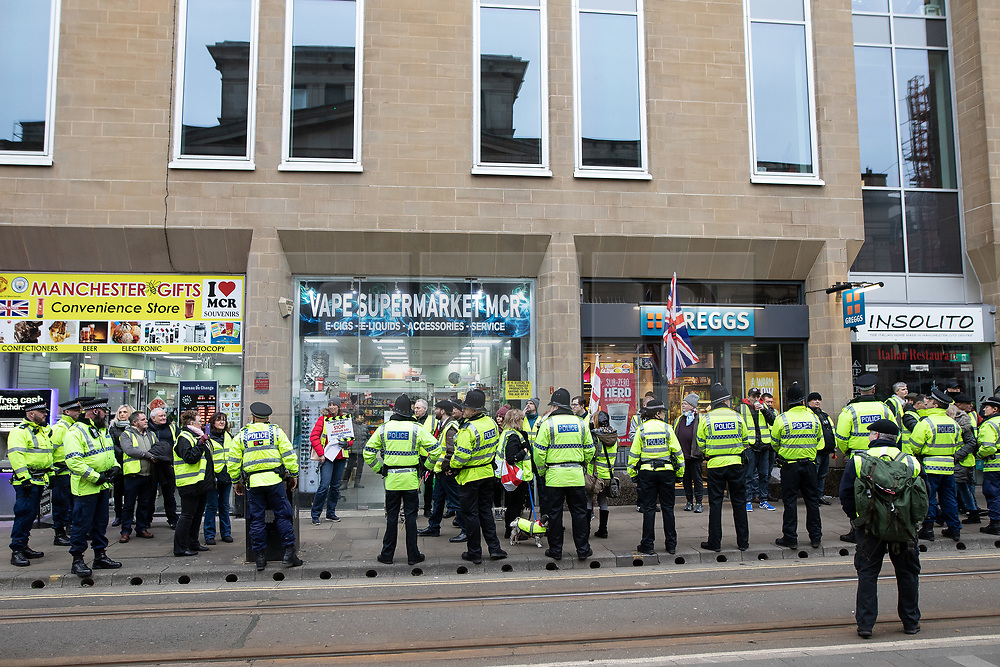 """© Licensed to London News Pictures . 05/01/2019. Manchester, UK. Protesters are kettled by police outside a branch of Greggs the baker on Mosley Street . A Yellow Vest demonstration takes place in central Manchester . The protest was organised via YouTube account """" Tommy Robinson News """" and was called in the wake of stabbings at Manchester Victoria Train Station on New Year's Eve . Protesters chanted in favour of Brexit , against police and press and carried pro-Trump and EDL clothing and placards . Photo credit : Joel Goodman/LNP"""