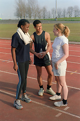 Multiracial group of teenagers standing talking at a race track,