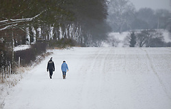 © Licensed to London News Pictures. 01/02/2019. Shiplake, UK. A couple walk in a snow covered field near Shiplake in South Oxfordshire after overnight snow falls and continuing low temperatures. Photo credit: Peter Macdiarmid/LNP