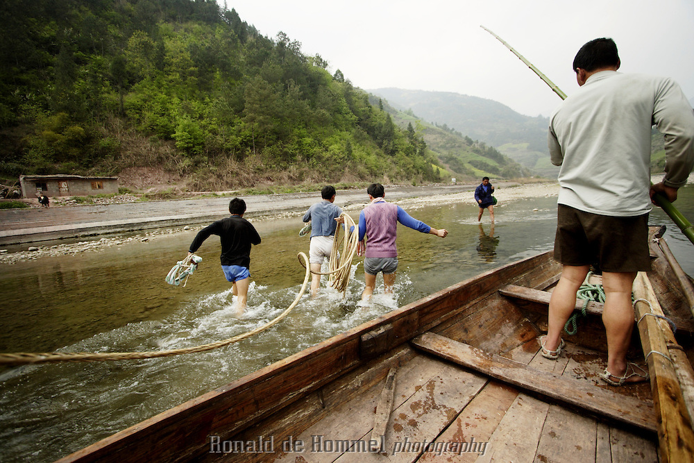 Pullers jump into the cold water of the Shennong stream to start pulling the boat upstream.