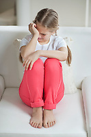 Little girl crying while sitting on sofa