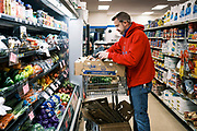 "03 AUGUST 2020 - JEWELL, IOWA:  GARREN ZANKER, manager of the Jewell Market, stocks the produce section. The only grocery store in Jewell, a small community in central Iowa, closed in 2019. It served four communities within a 20 mile radius of Jewell. Some of the town's residents created a cooperative to reopen the store. They sold shares to the co-op and  held fundraisers through the spring. Organizers raised about $225,000 and bought the store, which had its ""soft opening"" July 8. The store celebrated its official reopening Monday August 3. Before the reopening, Jewell had been a ""food desert"" for seven months. The USDA defines rural food deserts as having at least 500 people in a census tract living 10 miles from a large grocery store or supermarket. There is a convenience store in Jewell, but it sells mostly heavily processed, unhealthy snack foods that are high in fat, sugar, and salt.         PHOTO BY JACK KURTZ"