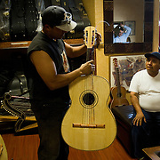 Tomas Delgado, world renowned for his craftsmanship in making and repairing guitars, tunes a guitar for a customer to try. Please contact Todd Bigelow directly with your licensing requests.