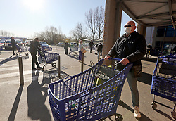 23 March 2020. Montreuil Sur Mer, Pas de Calais, France. <br /> Coronavirus - COVID-19 in Northern France.<br /> <br /> A man wearing a face mask to help protect herself from coronavirus iwaits in line outside Leclerc supermarket in Attin near Montreuil Sur Mer. Numbers entering the store at any one time are restricted to try and maintain 'social distancing,' in an effort to halt the spread of the virus. Anyone leaving their home must carry with them an 'attestation,' in a effect a self administered permit to allow them out of the house. If stopped by the police, one must produce a valid permit along with identification papers. Failure to do so is punishable with heavy fines. Movement in France has been heavily restricted by the government.<br /> <br /> Montreuil Sur Mer was the headquarters of the British Army under Field-Marshal Sir Douglas Haig from March 1916 to April 1919. Over 1,200 year old, the ancient fortified  town with its high ramparts has endured through history, surviving the plague and King Henry VIII's invasion of France in 1544 when the Duke of Norfolk under Henry VIII's command laid a disastrous siege to the town which held firm until Norfolk was forced to withdraw in 1545. Residents are confident the ancient town can survive the coronavirus too. <br /> Photo©; Charlie Varley/varleypix.com