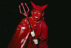 Portrait of child dressed in Halloween devil costume holding trident,