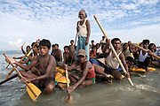 Sunday 12th November 2017. A Rohingya elder stands gracefully with staff in hand, giving direction. Men row steadily, without so much as a glance in the direction of a small group of photographers wading out to greet them.<br /> Women and children huddle together, quietly. The eight makeshift rafts, made of bamboo poles and yellow plastic palm oil containers, carry Rohingya refugees across the Naf River on a tide-dependent five-hour journey from Myanmar into Bangladesh. <br /> <br /> Often described as the &quot;world's most persecuted minority&quot;, the Rohingya are a Muslim ethnic group from the Rakhine State in Myanmar. In October 2016, a military crackdown in the wake of a deadly attack on an army post sent hundreds of thousands of Rohingya fleeing to neighboring Bangladesh. <br /> <br /> This most recent exodus from Rakhine state, Myanmar, to the makeshift camps that have sprung up in Cox&rsquo;s Bazar District, began August 25, 2017, when militants from the Arakan Rohingya Salvation Army targeted about 30 police posts and an army base, killing several people. <br /> <br /> So far more than 650,000 people have fled into Bangladesh, swelling the camps and creating a humanitarian crisis. Photograph by David Dare Parker