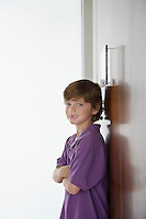 Boy (7-9) leaning on wardrobe and smiling