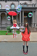 Auburn ballerina, dressed with a white tutu, red rain boots and a red umbrella, dances next to a mysterious brunette girl with a trench coat.