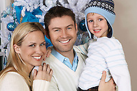Couple with son (5-6) in front of Christmas tree, portrait