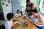 "Jill McTighe (right), a mother and school aide,  enjoys dinner with her husband Earl Gillespie and their children at their home in Willesden, London, United Kingdom. (From the book What I Eat: Around the World in 80 Diets.) The caloric value of her day's worth of food on a ""bingeing"" day in the month of September was 12300 kcals. The calorie total is not a daily caloric average.  Jill is  31 years old; 5 feet, 5 inches tall;  and 230 pounds. Honest about her food addiction replacing a drug habit, Jill joked about being a chocoholic as she enthusiastically downed a piece of chocolate cake at the end of the photo session. Her weight has yo-yoed over the years and at the time of the picture she was near her heaviest; walking her children to school every day was the sole reason she didn't weigh more. She says this photo experience was a catalyst for beginning a healthier diet for herself and her family. Jill herself is MODEL RELEASED  [Use of Jill McTighe images must be used contextually only and use cleared with Peter Menzel Photography on a case by case basis.]"