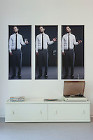 Triptych above record player on painted sideboard
