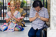 29 FEBRUARY 2008 -- BANGKOK, THAILAND: A woman prays while classical Thai dancers perform behind her at the Erawan Shrine in Bangkok, Thailand. The Erawan Shrine is a Hindu shrine that houses a statue of Phra Phrom, the Thai representation of the Hindu creation god Brahma. A popular tourist attraction, it often features performances by resident Thai dance troupes, who are hired by worshippers in return for seeing their prayers at the shrine answered. The Erawan Shrine was built in 1956 as part of the government-owned Erawan Hotel to correct bad omens believed to be caused by laying the foundations on the wrong date.   Photo by Jack Kurtz