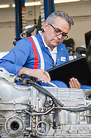 Senior mechanic analyzing car engine and holding clipboard