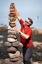 Dunbar, Scotland, UK. 20 April, 2019. Competitors in the 30 minutes most stones height event on Eye Cave beach in Dunbar during opening day of the European Stone Stacking Championship 2019.