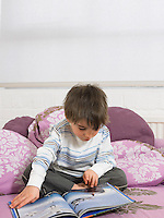 Boy (5-6) reading book on couch in living room
