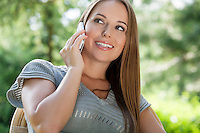 Beautiful young woman using mobile phone in park