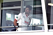 Alastair Cook of Essex look out from the team balcony during the delay the start of play after a heavy rain shower this morning ahead of the Specsavers County Champ Div 1 match between Somerset County Cricket Club and Essex County Cricket Club at the Cooper Associates County Ground, Taunton, United Kingdom on 26 September 2019.