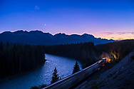 The close conjunction of the waxing crescent Moon near Venus in the evening sky, from the Storm Mountain viewpoint on the Bow Valley Parkway in Banff National Park, Alberta, on July 15, 2018. Taken with a westbound train heading toward the Divide. <br /> <br /> The mountains to the west define the Continental Divide. The Bow River and the CPR tracks wind off into the distance.<br /> <br /> This is a 5-exposure HDR blend using Adobe Camera Raw. Taken with the Canon 35mm lens and Sony a7III camera.