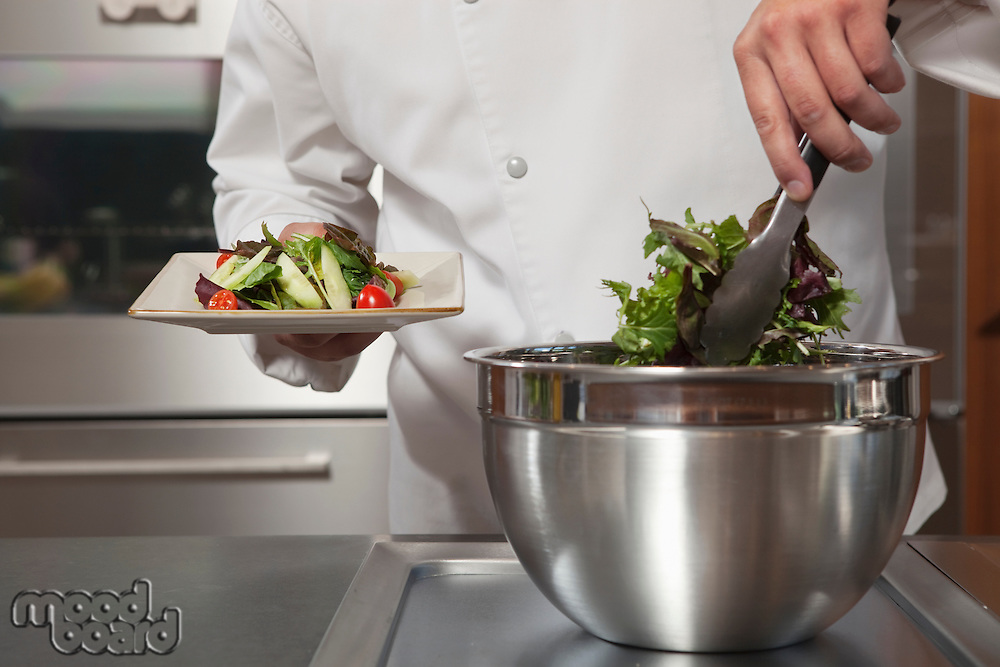 Mid- adult chef lifts leaf vegetables onto side plate