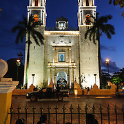 A group of people sit across the street from the twin steeples of the Spanish colonial Cathedral of San Gervasio (Catedral De San Gervasio) at dusk. The Cathedral is next the main square in downtown Valladolid, in the heart of Mexico's Yucatan Peninsula.