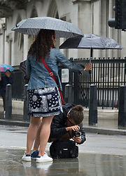 © Licensed to London News Pictures. 02/08/2016. London, UK. A visitor holds an umbrella as another takes a photo near Parliament as intermittent rain showers hit the capital. Photo credit: Peter Macdiarmid/LNP