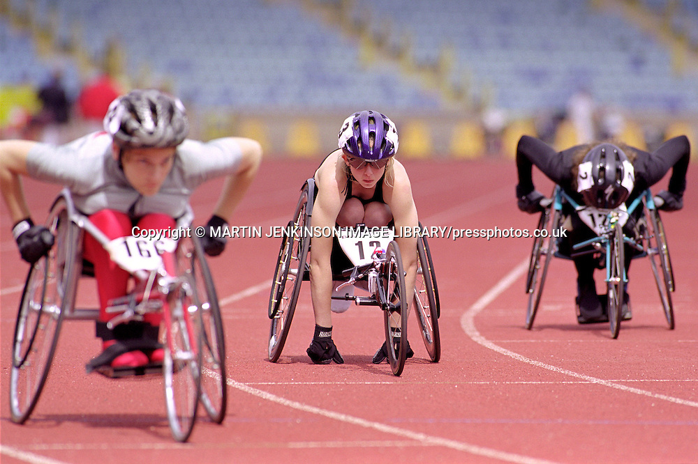 Female wheelchair racers line up at the start of a race.