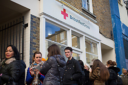 © licensed to London News Pictures. London, UK 22/11/2013. People queuing outside the British Red Cross branch in Chelsea, London to buy items donated by David and Victoria Beckham to help raise money for Philippine typhoon disaster. Photo credit: Tolga Akmen/LNP
