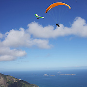 Hang gliders and para gliders fly high the hillside of Pedro Bonita high in the hills of Rio de Janeiro. Pilots of hang gliders and para gliders take tourists for tandem flights with breathtaking views of the city before landing on Sao Conrado beach. Rio de Janeiro,  Brazil. 9th September 2010. Photo Tim Clayton