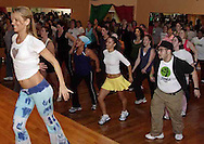 Natalie Garcia (on stage, left) from Miami leads a group including Frank Suarez (front row, right) and Maria Browning (on Frank's left) during the grand opening of Studio Zumba in Vandalia, Sunday, January 28, 2007.  Frank and Maria are Zumba instructors in Lexington and came up for the grand opening.