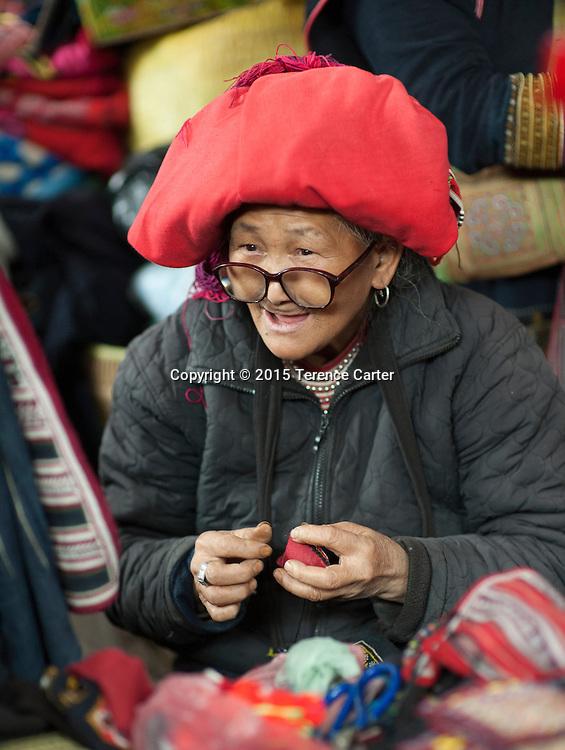A hilltribe woman sews a local garment in the markets in Sapa, Vietnam.