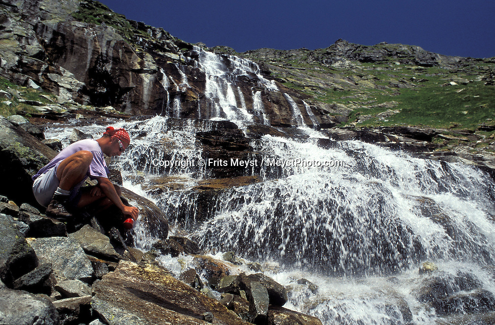 AUSTRIA, HIGH TAUERN NATIONAL PARK, JULY 2000. Filling up the water bottle at one of the cleanest water supplies.  The Hohe Tauern mountains are one of the most spectacular mountain regions in Austria, where one can trek from hut to hut over glaciers and regular trails as well as high mountains. Photo by Frits Meyst/Adventure4ever.com