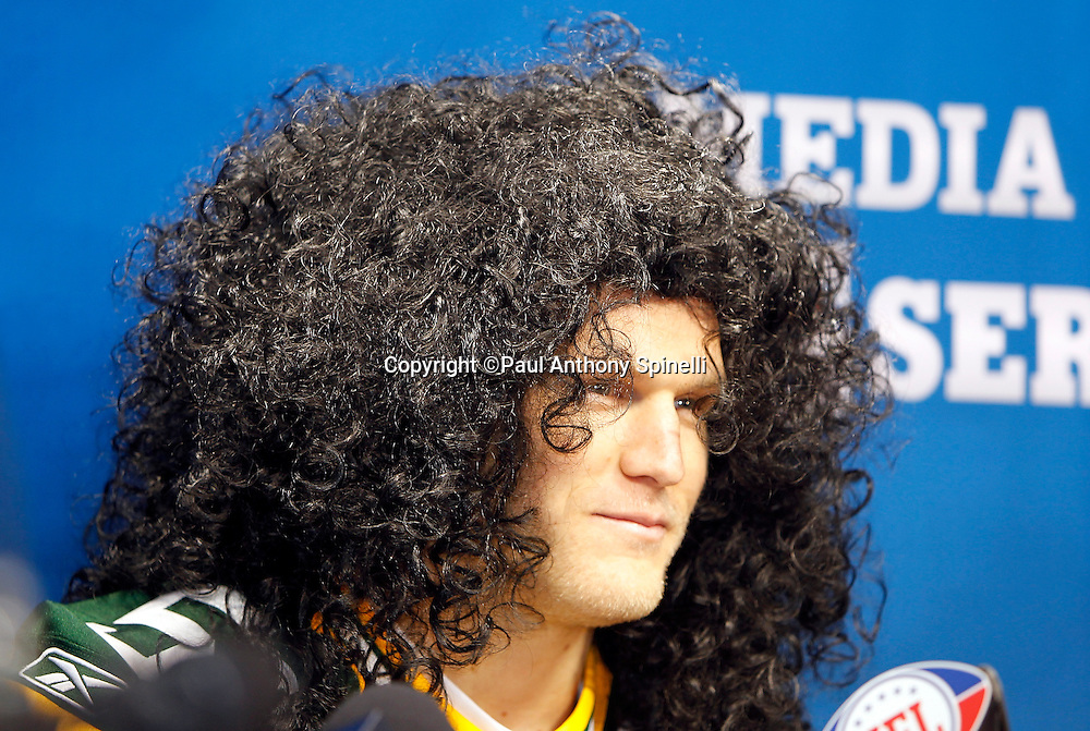 Green Bay Packers linebacker Clay Matthews (52) dons a wig given to him by a media member with hair like Pittsburgh Steelers safety Troy Polamalu (43) as he speaks to the press at Super Bowl XLV media day prior to NFL Super Bowl XLV against the Pittsburgh Steelers. Media day was held on Tuesday, February 1, 2011 in Arlington, Texas. ©Paul Anthony Spinelli