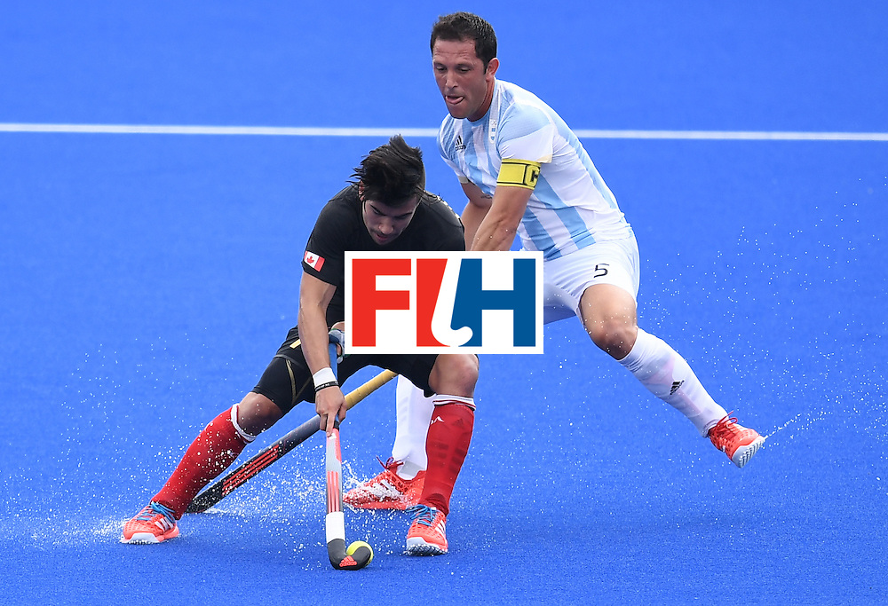 Argentina's Pedro Ibarra (R) vies for the ball with Canada's Gabriel Ho-Garcia during the men's field hockey Canada vs Argentina match of the Rio 2016 Olympics Games at the Olympic Hockey Centre in Rio de Janeiro on August, 8 2016. / AFP / MANAN VATSYAYANA        (Photo credit should read MANAN VATSYAYANA/AFP/Getty Images)