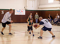 Jayda Glines gets around Chris Noyes during the community basketball game between Holy Trinity students and the Laconia Police Dept on Saturday morning.  (Karen Bobotas/for the Laconia Daily Sun)